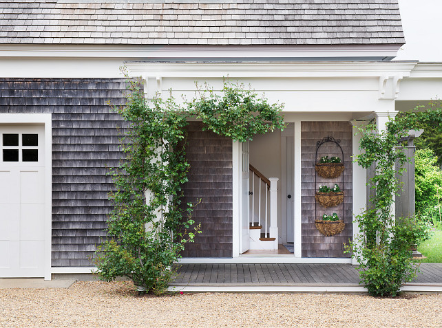 Garden. Beach House Garden. Cottage Garden. Climbing plants. Flower baskets. Gravel driveway. Wall mounted baskets. Weathered wood. Shingle siding. White columns. White door. White fascia