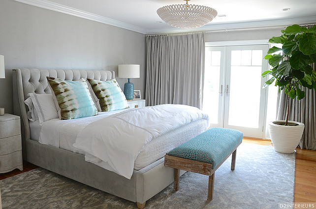 Gray Bedroom. Gray Bedroom Design. Stunning gray bedroom accented with pops of turquoise blue features gray walls alongside French doors dressed in gray silk drapes illuminated by an Oly Studio Pipa Bowl Chandelier. A weathered bench with turquoise cushion stands at the foot of the gray velvet bed with tufted headboard which is dressed in white and gray hotel bedding and aqua blue tie dye pillows flanked by Studio A Toile Linen Chests topped with AERIN Culloden Table Lamps atop a gray ikat rug.