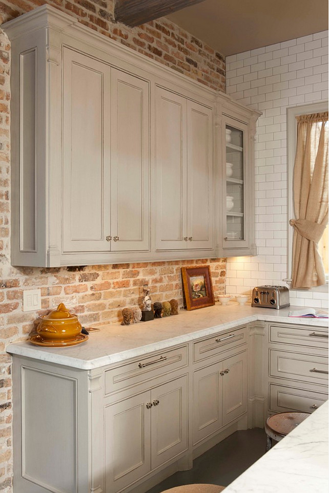 Gray Kitchen. Gray kitchen cabinet with brick backsplash wall and honed Carrara countertop. Whitestone Builders.