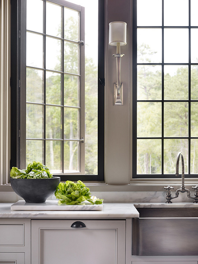 Gray Kitchen. Kitchen features gray cabinets paired with white marble countertops fitted with a stainless steel apron sink and deck-mount gooseneck faucet and Ruhlmann Single Sconces. #Kitchen #GrayKitchen Dungan Nequette