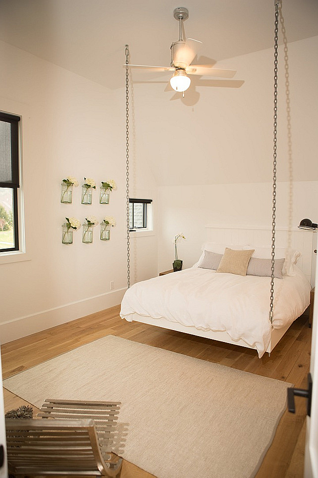 Hanging Bed. Chain Hanging Bed Ideas. Cottage Bedroom features a hanging bed suspended from the ceiling by chains next to a wall of stacked vases filled with flowers. #HangingBed Hahn Builders.