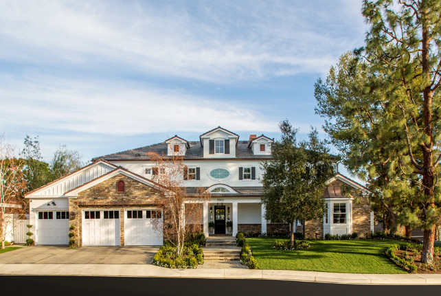 Home Exterior. Home Exterior black shutters covered porch eyebrow dormer window front yard gable dormer window gable roof landscaping stone siding three car garage white square columns
