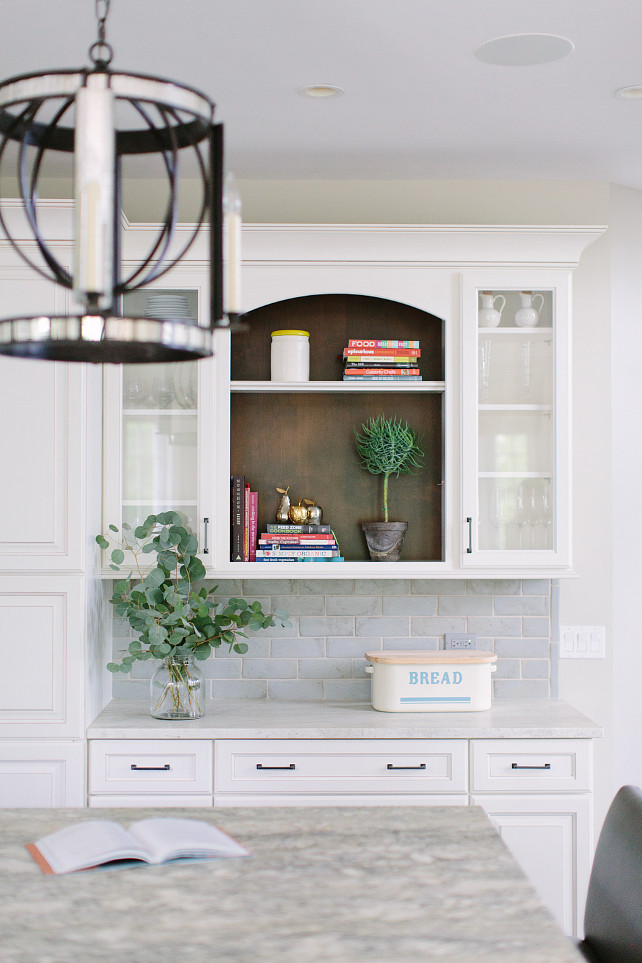 Kitchen Bookshelf Cabinet. Beautiful kitchen features bookshelf cabinet, white raised panel cabinets paired with white marble countertops and a blue beveled subway tiled backsplash. Kate Marker Interiors.