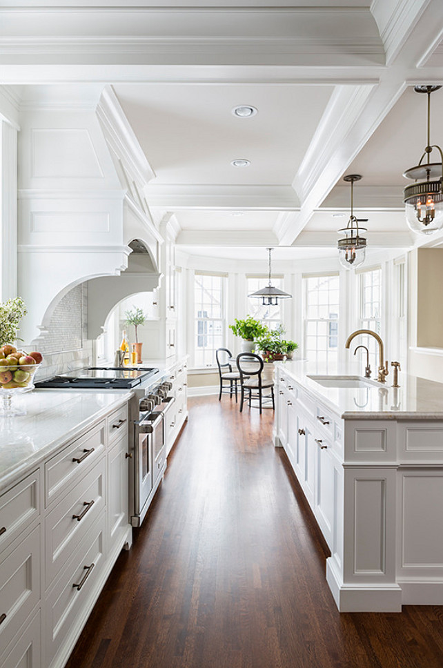 Kitchen Cabinet. Kitchen features a pair of The Urban Electric Co Dover Bell lights illuminating a long center island topped with white marble. #Kitchen  #KitchenLighting   Casa Verde Design.