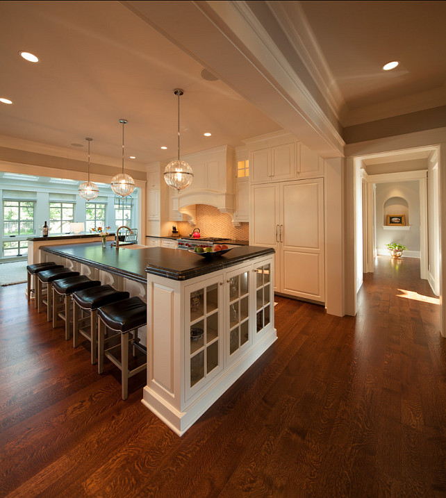 """Kitchen Design. The floors are 5"""" Rift & Quarter Sawn White Oak, Select Grade, with a custom-blended stain. Kitchen Pendants are """"Janus globe pendant from Cyan Design"""". Cabinets are painted in Benjamin Moore White Dove OC17. #KitchenDesign #Kitchen #KitchenIdeas #WhiteKicthen"""