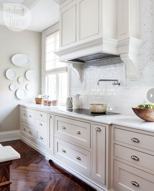 Kitchen Ideas. Kitchen with white cabinets, custom kitchen hood, white subway tiles, polished nickel pulls and reclaimed elm hardwood floors laid in a herringbone pattern. #kitchen Style at Home via Pintucks & Peonies.