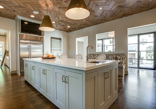 Kitchen Lighting. Amazing kitchen features a wood herringbone ceiling accented with Goodman Hanging Lamps illuminating a gray kitchen island. #Kitchen #KitchenLighting Avrea Wagner Interiors.
