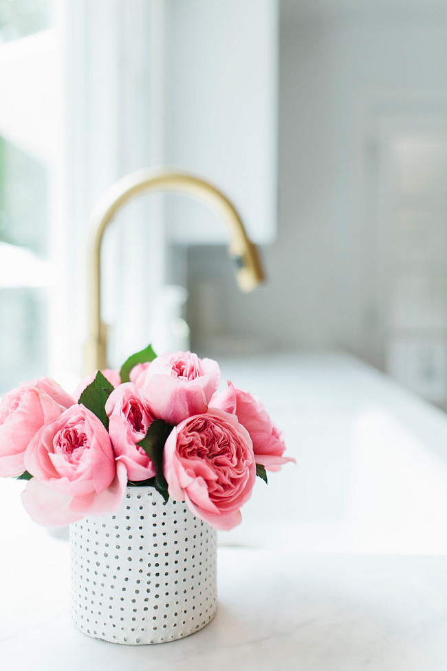 Kitchen Pink Peonies. Beautiful pink peonies in kitchen with white marble countertop and gold kitchen faucet. #kitchen #PinkPeonies #WhiteMarble #GoldFaucet #KitchenFaucet Shea McGee Design.