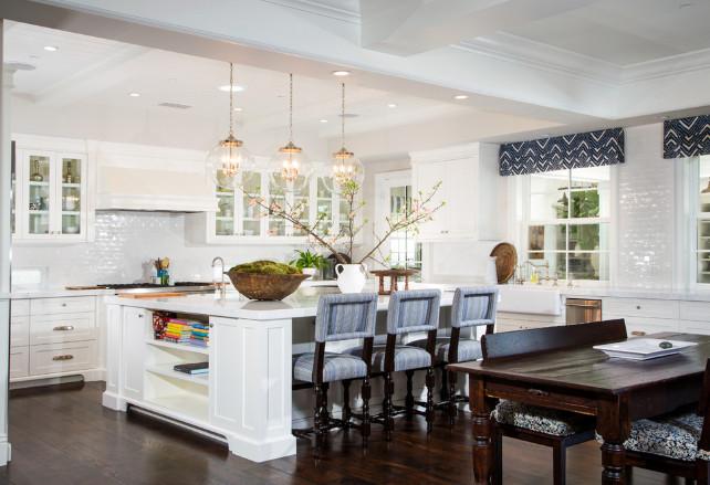 Kitchen layout. Open kitchen layout. Glass-front kitchen cabinets flank paneled range hood over glossy white mini subway tiled backsplash above stainless steel stove. #OpenKitchen #OpenKitchenLayout