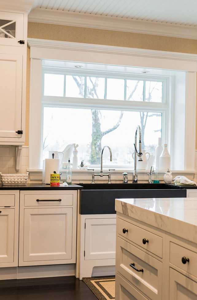 Kitchen sink with two faucets. #Kitchen #Sink #Faucets A transitional black apron sink is paired with a bridge gooseneck faucet and a pull-out spray faucet. The kitchen island is topped with thick marble countertop contrasting with espresso hardood floors. Brookes and Hill Custom Builders.