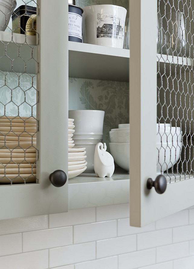 Kitchen with Chicken Wire Cabinet Doors. This kitchen boasts upper cabinets, with backs of shelves lined with gray damask wallpaper, accented with chicken wire doors.  Jenny Wolf Interiors.