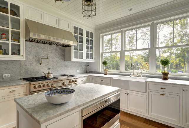 "Kitchen with marble slab backsplash. Kitchen with white gray marble slab backsplash.  This lovely cottage kitchen features creamy white shaker cabinets paired with gray marble countertops and a gray marble slab backsplash.  The kitchen also features beadboard ceiling, a small kitchen island fitted with microwave and a farmhouse sink with deck mount bridge faucet. The range stands under a stainless steel hood flanked by glass-front cabinets.  Kitchen lighting are the ""Ralph Lauren Crosby Medium Flush Mount In Polished Nickel"".#Kitchen #kitchenMarbleSlabBacksplash #SlabBacksplashJohn Hummel and Associates."