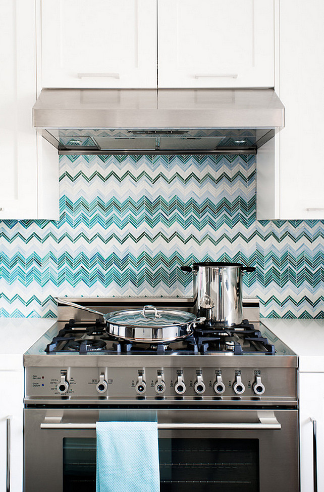 Kitchen. Backsplash. Blue chevron backsplash, chevron backsplash, green chevron backsplash, range hood, stainless steel, stainless steel range, white cabinets, white countertop. Backsplash is a custom designed glass tile. Jute Interior Design.