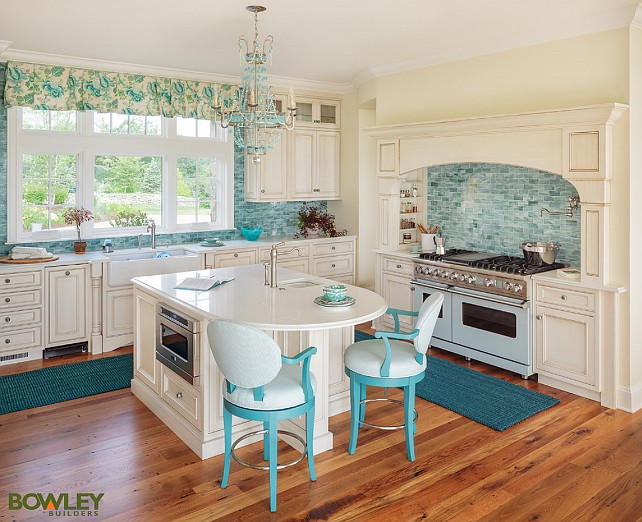Kitchen. Coastal Kitchen with creamy white cabinets, turquoise backsplash, turquoise chandelier, turquoise counterstools and turquoise roman shades. #Kitchen #CreamyWhiteKitchen #TurquoiseKitchen #Turquoise Bowley Builders