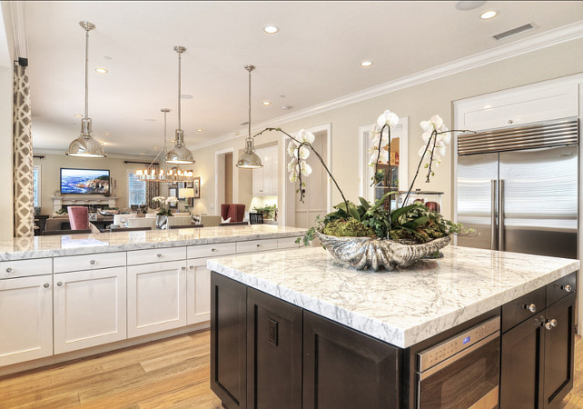 Kitchen. Kitchen Island Ideas. Kitchen Island Design. Kitchen. White and gray granite countertops sit atop white cabinets and a large, dark wood island. #Kitchen #KitchenIsland #KitchenIdeas