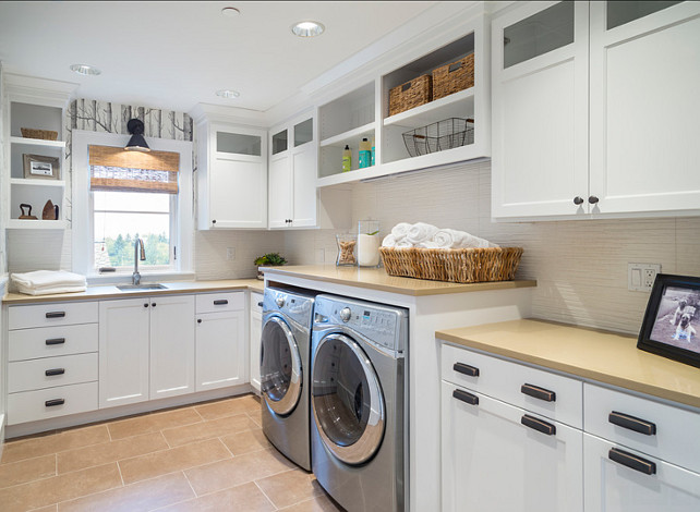 "Laundry Room Ideas. Laundry Room Cabinet Ideas. This laundry room features birch wallpaper, slab quartz, open shelves, lighting by Hudson valley, washer & dryer, ORB cup pulls, glass cabinet doors, tile floors and textured white tile backsplash.  Countertop is ""Caesarstone 2370 Mocha"". #LaundryRoom #LaundryRoomCabinet"