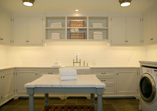 Laundry Room. Second Floor Laundry. Chic large 2nd floor laundry room design with white cabinets, gray laundry room island, calcutta gold counter tops, beveled subway tiles backsplash, farmhouse sink, and white washer & dryer. #LaundryRoom #LaundryRoomDesign  Giannetti Home.