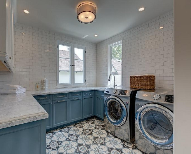Laundry Room. Blue and white laundry room. Two toned laundry room cabinets. Two toned laundry room cabinets painted in blue and white, white subway tiles and cement tile flooring. Sotheby's Homes.