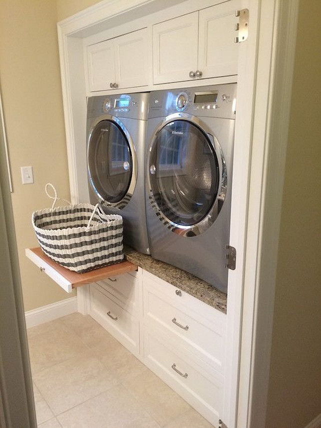 Laundry Room. Laundry Room Ideas. Laundry room machine ideas that are easy on your back. Enclosed Washer and Dryer | Laundry room features built-in cabinets encasing a silver front-load washer and dryer accented with pull out trays sandwiched between cabinets above and stacked drawers below. Via Decorpad.