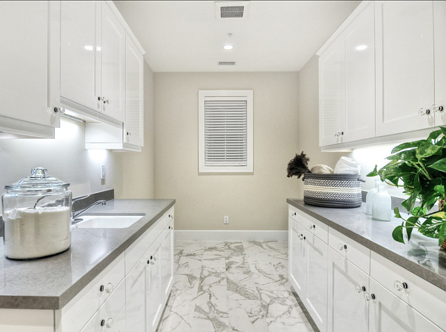 Laundry Room. Laundry Room Ideas. Bright, shiny, white cabinets create a clean look in this spacious laundry room. #LaundryRoom #LaundryRoomIdeas #LaundryRoomDesign #LaundryRoomCabinet #LaundryRoomCountertop