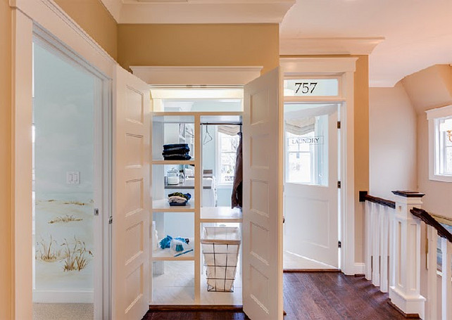 "Laundry Room.  Pass-through shelving accessible both from inside the laundry room and from just outside provides ""get it yourself"" convenience.  This is such a smart idea! I would love to incorporate it at home. I might would want to make each shelf wider to place laundry baskets. Every family member would have their own shelf. Laundry Room Ideas. #laundryRoom #laundryRoomIdeas"