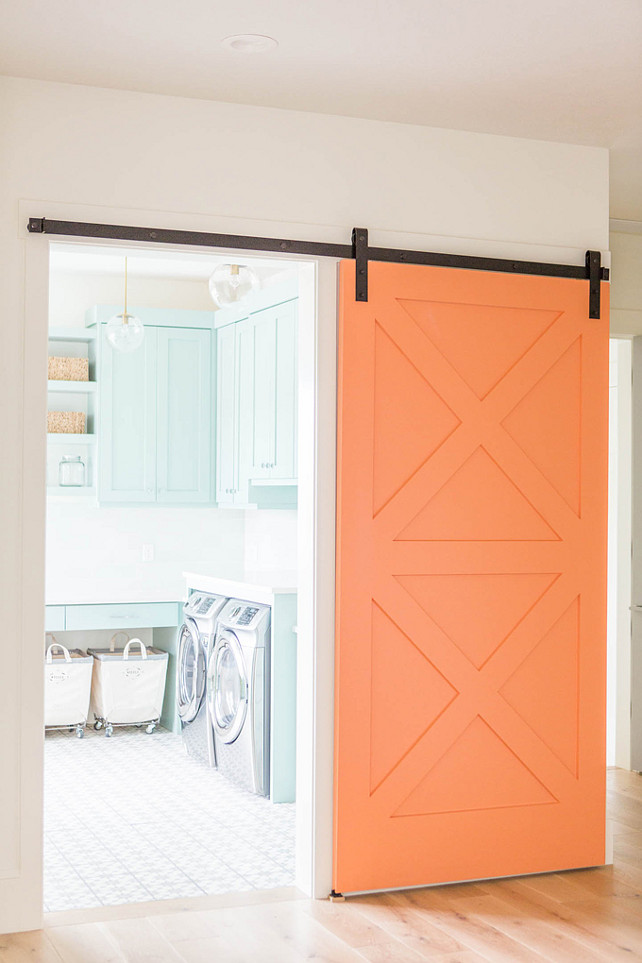 Laundry room with barn door. Laundry room with barn door ideas. An orange barn door on rails slides open to reveal a laundry room. #LaundryRoom #BarnDoor  Ashley Winn Design.