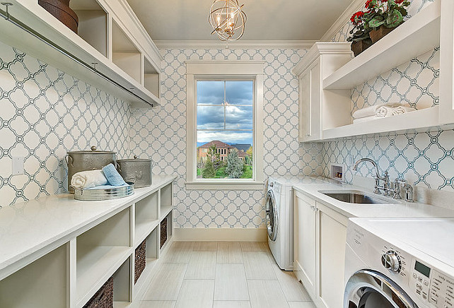 Laundry room. Galley style laundry room with blue quatrefoil wallpaper. Do you like having the laundry machines separate? It's not very practical in my opinion.  Clark and Co Homes.