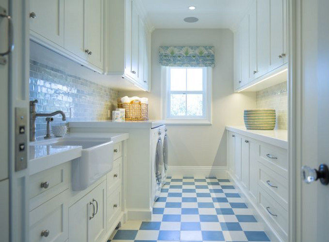Laundry room. Laundry room with checkered floors. Laundry room. Laundry room with checkered floors. #checkeredfloors #laundryroom Kelly Nutt Design. Great white and blue laundry rooms featuring white shaker cabinets paired with glazed blue tiled backsplash atop white and blue checkered tiled floor. A farmhouse laundry room sink paired with stain nickel faucet stands next to a white front-load washer and dryer across from a laundry folding station. #checkeredfloors #laundryroom Kelly Nutt Design.
