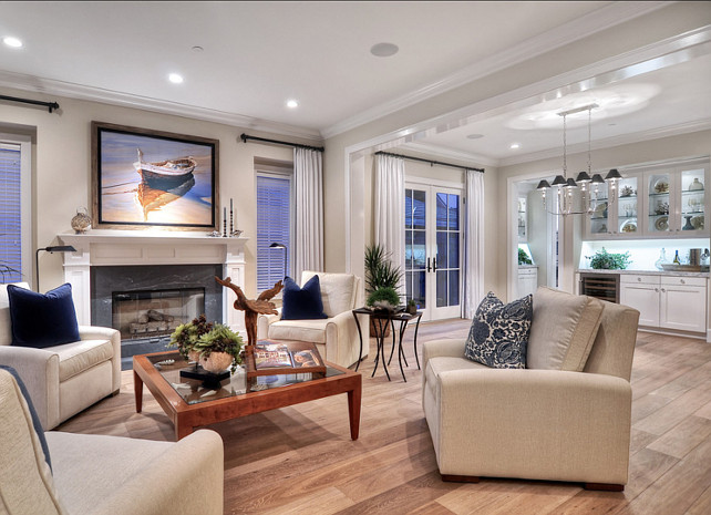 """Benjamin Moore HC-80 Bleeker Beige"". Living Room Ideas. Beach accents and artwork create a coastal feel in this bright and open living room. Off white, oversized occasional chairs surround a glass topped wooden table.  #LivingRoom"