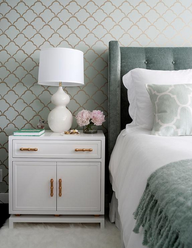 Master Bedroom Bedding Ideas. Grey bedroom features an accent wall clad in green and gold scallops wallpaper lined with a gray velvet wingback headboard on bed dressed in white scalloped bedding, green Moroccan tiles pillows in Windsor Smith Riad Fabric and a gray fringed throw blanket. A gray tufted headboard stands next to a white nightstand with gold bamboo pulls, Worlds Away Marcus White & Gold Leaf Cabinet, topped with a white glass lamp atop a white sheepskin rug.