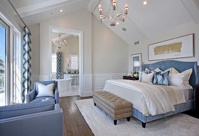Master Bedroom with blue wing bed, blue chairs, ivory rug area, creamy white walls and a stunning polished nickel chandelier. #Bedroom #MasterBedroom Spinnaker Development.
