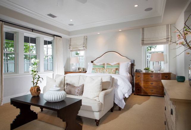 Master bedroom. Master bedroom design. Great idea of adding a natural linen settee. Notice the damask pillows and espresso coffee table. This beautiful master bedroom features arched bed dressed in soft white bedding and gray and mint green striped pillows flanked by traditional nightstands placed under windows. The windows are dressed in gray grosgrain roman shades. #MasterBedroom Legacy Custom Homes, Inc.