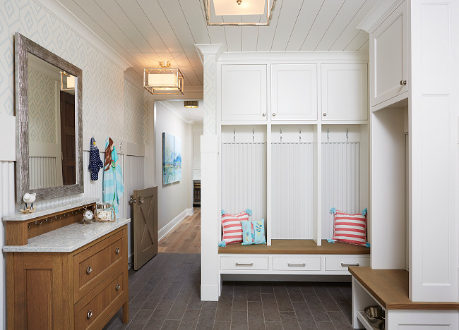 Mudroom. Mudroom with dark gray porcelain tiles, individual cubbies with drawers, cabinet and hooks. A dresser adds extra storage space to this mudroom. Blend Interior Design.