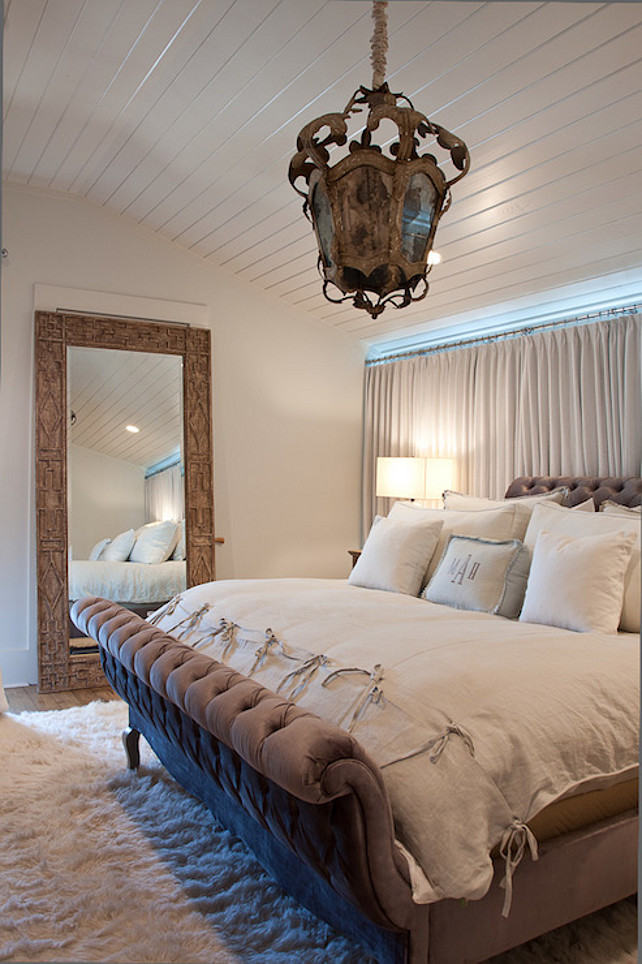 Neutral Bedroom with Floor Mirror. Neutral bedroom bedroom features antique lantern over gray velvet tufted sleigh bed dressed in white linen bedding over white sheepskin rug. Beachy bedroom with beadboard paneled barrel ceiling accented with light gray curtains behind headboard as well as carved wood floor mirror.  #NeutralBedroom #Bedroom Romair Homes.