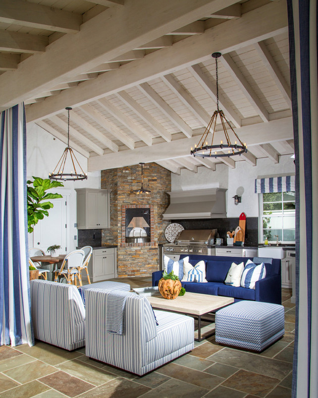 Outdoor Living Area. Outdoor living area with comfortable outdoor furniture. The living room opens to an outdoor living area that features a TV on stone fireplace flanked by gray built-in bookcases illuminated by oil-rubbed bronze vintage lanterns across from blue sofa facing white and gray striped slipper chairs accented with navy blue pillows across from industrial coffee table atop slate tiled floor. Legacy Custom Homes, Inc.