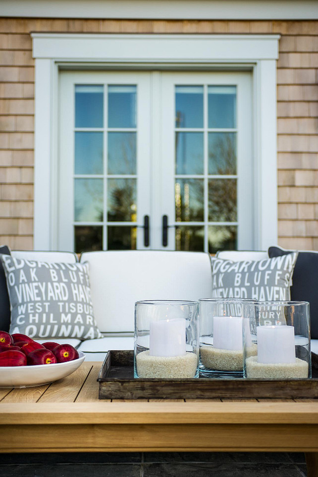 Patio Decorating Ideas. The teak furniture and white cushions echo the home's neutral coloring, serving as a complimentary extension to the Cape Cod abode. #PatioFurniture #PatioIdeas