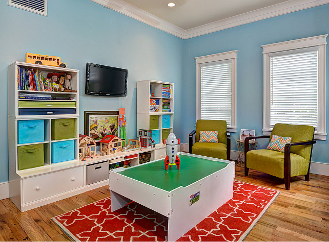 Playroom. chevron pillows, green armchairs, open shelves, Play Table, recessed lighting, red and white area rug, storage bins, toy storage, wall mounted TV, white blinds, white shelving unit, white trim