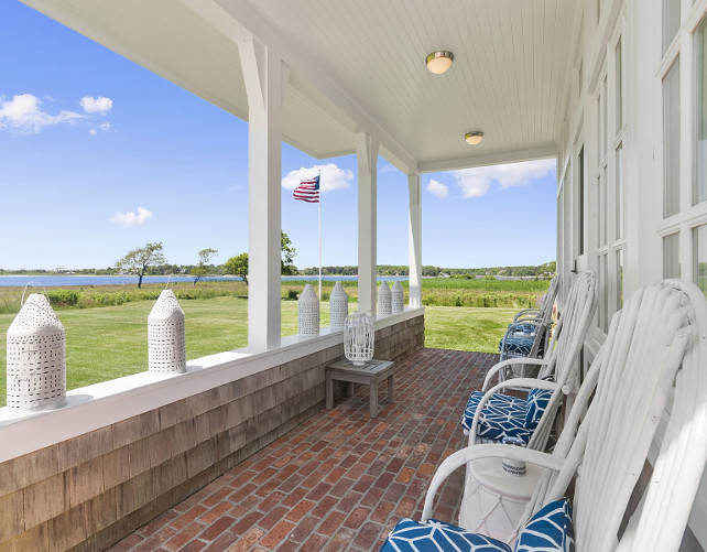 Porch Chair Ideas. Beach cottage porch with white chairs with cushions. Brick flooring porch. Beadboard ceiling porch. Porch Lanterns. American flag porch. #Porch
