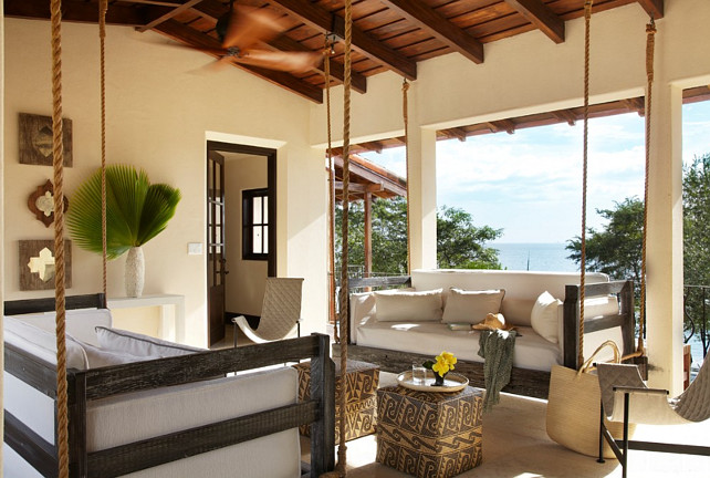 Porch Swing. Two porch swings facing each other in this porch with ocean view.  Interior Design by Beth Webb Interiors.