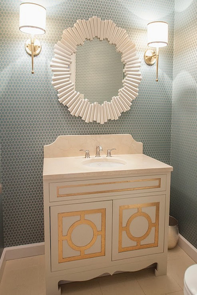Powder Room. Powder Room Design. Transitional Powder Room. Chic powder room features walls clad in blue and ivory geometric wallpaper which frame a Charles Round White Mirror flanked by contemporary sconces over a custom vanity accented with gold leaf molding light stone counter and a matching backsplash. #PowderRoom  Lucy and Company