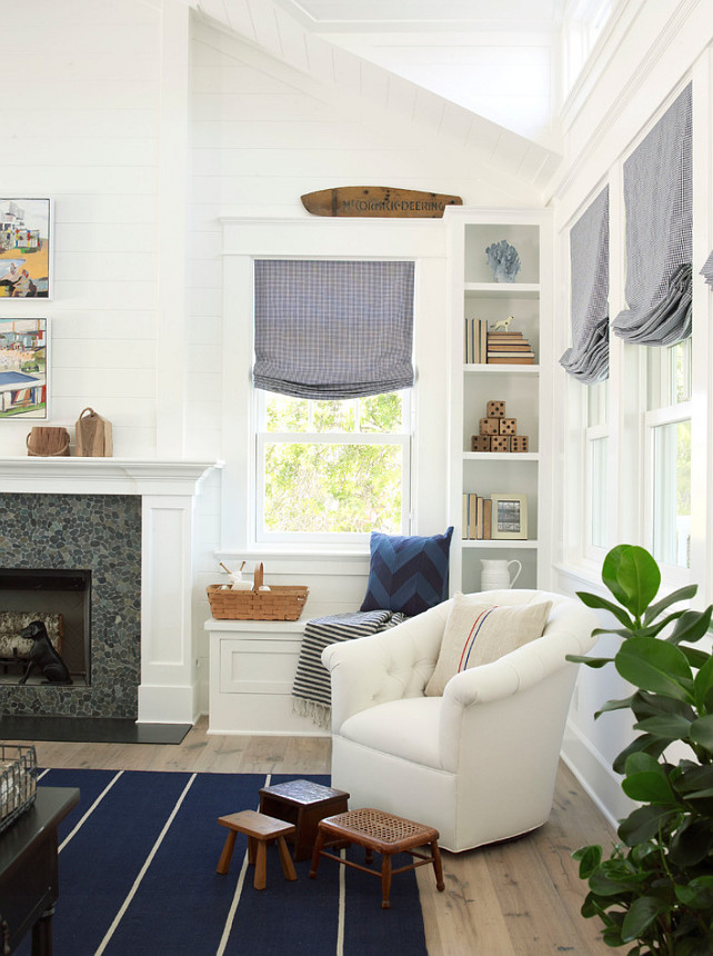 "Reading Nook. Reading Nook with built-in window seat and comfortable white tufted chair paired with a collection of vintage stools placed atop navy blue striped rug. #ReadingNook #Furniture Paint Color: ""Pratt and Lambert Designer White"". Burnham Design."