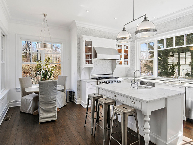 Small Crisp white kitchen with breakfast nook. Via Sotheby's Homes.