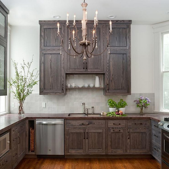 Small Kitchen. Small Kitchen with Burnt Oak Cabinets. Small kitchen features a French candle chandelier illuminating dark stained cabinets paired with a dark stained wood countertop and a gray tiled backsplash. #SmallKitchen #Kitchen #BurntOak #BurntOakCabinet K G Bell