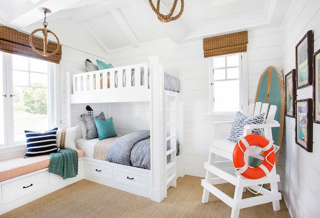 Tongue and groove bunk room. This white Bunk room features white bunk bed with gray bedding, turquoise decorative pillows, rope pendant lighting, bamboo shades, window seat, sisal carpeting and shiplap walls. Coastal bunk room with tongue and groove walls. #Bunkroom #TongueandGroove #CoastalInteriors Blackband Design.