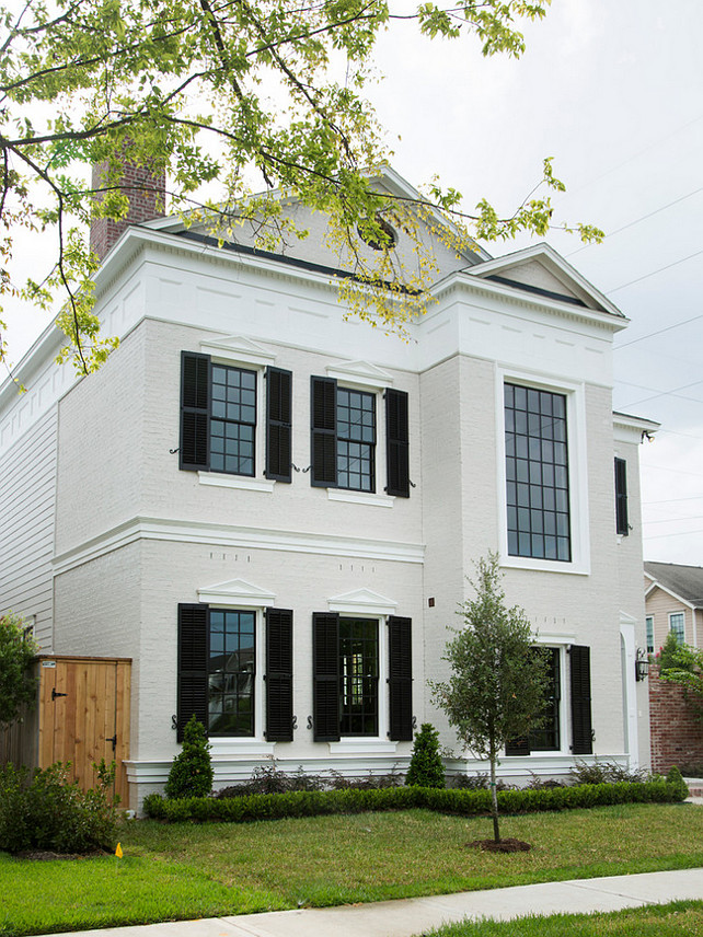 Traditional home with white exterior and black window shutters. #TraditionalHome #HomeExterior #WhiteExterior #BlackShutters Whitestone Builders.