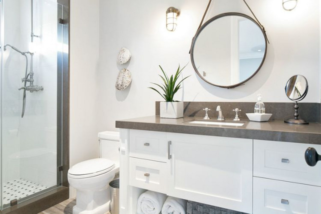 Transitional Bathroom. This transitional bathroom features leather captain's mirror illuminated by nautical sconces. The washstand is topped with gray quartz countertop. Kelly Nutt Design.
