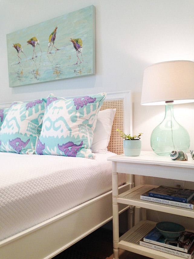 Coastal Bedroom. Coastal bedroom features art over a cane bed dressed in white bedding and aqua and purple ikat pillows next to a white bamboo nightstand with cane shelves topped with a recycled glass lamp. #Bedroom #CoastalBedroom Meredith McBrearty