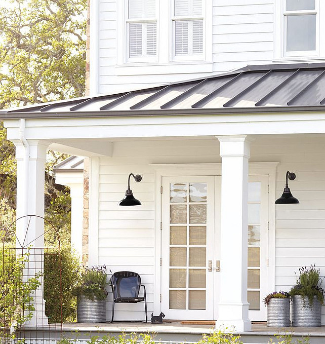 White Exterior Siding Ideas. Metal roof, lanterns and planters. Cassic white house with black accents. Via Rejunenation.