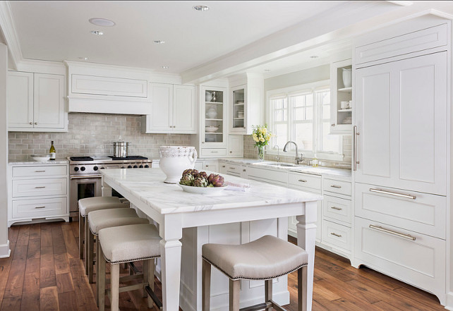 White Kitchen. Classic white kitchen with inset cabinets painted Benjamin Moore Simply White accented with brushed nickel pulls and calcutta countertops with an Encore Silver Ceramic Tiled backsplash. U-shaped kitchen with inset cabinets painted Benjamin Moore Simply White accented with brushed nickel pulls and calcutta countertops with an Encore Silver Ceramic Tiled backsplash. A dual stainless steel range stands at the far end of the island finished with a paneled range hood. The kitchen features a stainless steel undermount sink with gooseneck faucet situated below a triple sash window with glass front cabinets either side next to a cabinet front refrigerator. The long kitchen island is lined with Hickory Chair Madigan Counter Stools which are tucked below the countertop overhang. #kitchen #Whitekitchen #classickitchen #benjaminMooreSimplyWhite