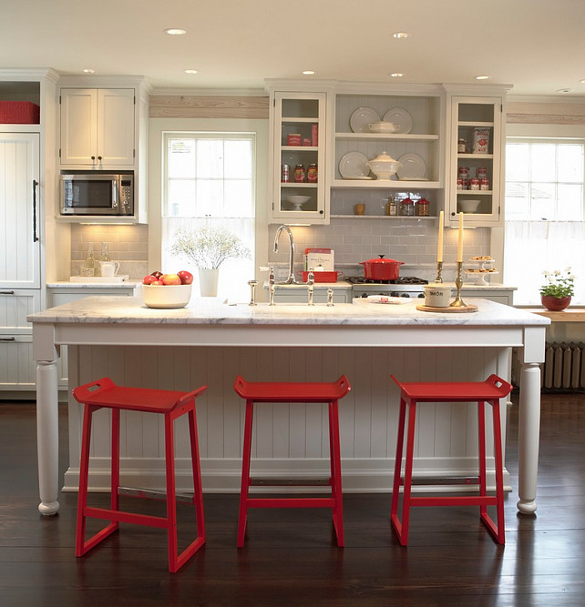 White Kitchen with pops of red. White kitchen with red decor. White Kitchen with red counterstools and decor. The subway tile backsplash is Waterworks Architectonics 3x6 in Dove. White Kitchen and red. #WhiteKitchen Meriwether Inc.